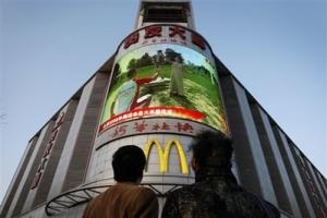 昨日在有人在北京街頭的電視大螢幕上觀賞希臘燃點奧運聖火儀式的現場直播。(圖:美聯社) <br/>