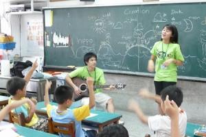 矽谷生命河靈糧堂短宣隊員張晟恩彈著吉他和伙伴一起進行美語詩歌帶動唱。 (圖: 一粒麥子提供) <br/>