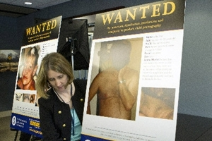 USICE公關人員豎立嫌犯容貌的看板。(圖:美聯社) <br/>