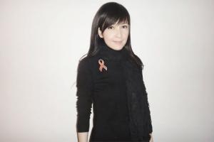 周慧敏扣上紅絲帶, 用行動表達對愛滋病的關注以及對感染者的支持。(圖:香港愛滋病基金會) <br/>