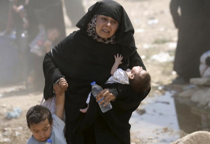 一位敘利亞女人帶著孩子越過土耳其邊界避難。土耳其官方表示,剛在星期天重開關閉多日的邊界,估計將有1萬人從敘利亞過境避難。(圖: 路透社)