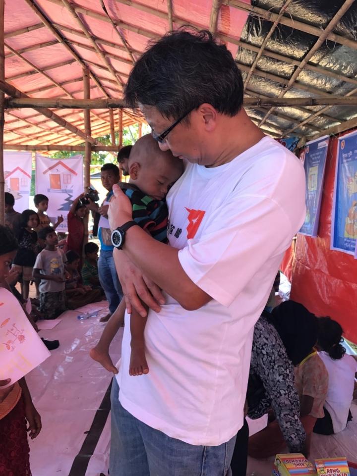 趙煥明抱著八個月大極度養不良的嬰孩,體重如如初生嬰兒。