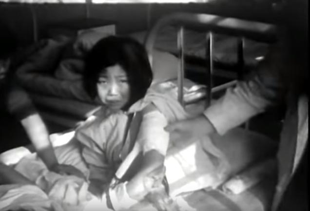 影片中的女孩被日軍傷手肘,父母亦死於槍下。(圖:約翰·馬吉拍攝實錄視頻)