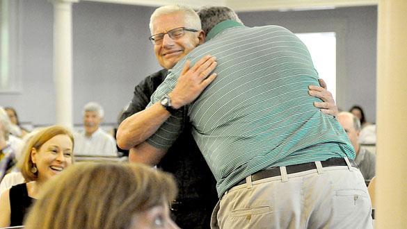 新帕爾茲改革教會牧師霍華德梅傑在他的退休派對上被一位社區居民擁抱歡迎。 他已經服事教會28年。 (圖: Lauren Thomas)