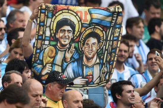阿根廷球迷舉起印有美斯和馬勒當拿上帝形象的旗幟。(圖:網絡圖片)