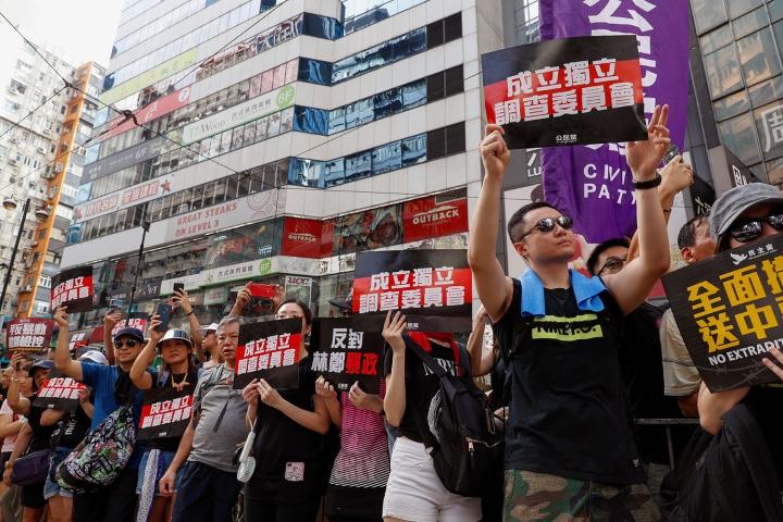 示威者在反送中遊行舉起成立獨立調查委員會標語。(圖:美聯社)