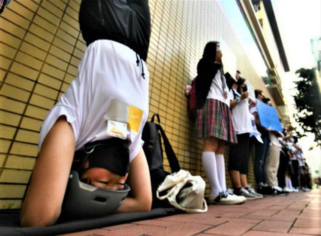 銅鑼灣聖保祿學生「倒立」控訴世界「黑白顛倒」。(圖:視頻擷圖)