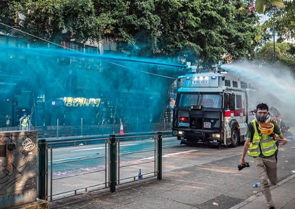 警方發射藍色催淚液體,記者走避。(圖:Studio Incendo)