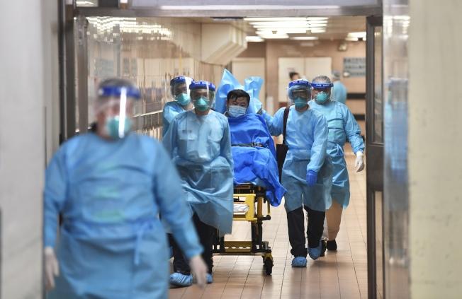 醫護人員轉送武漢肺炎患者至瑪嘉烈醫院。(圖:中通社)