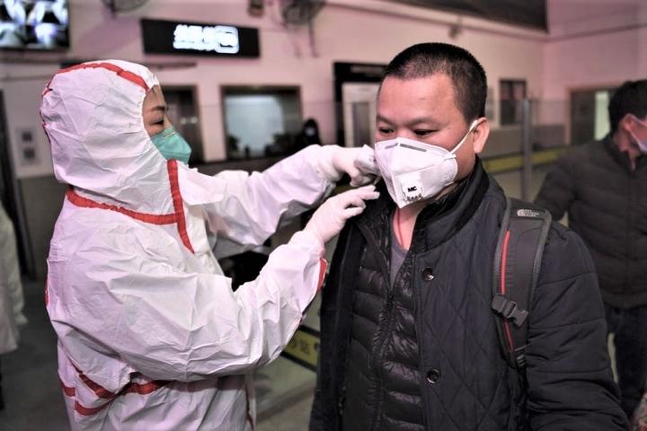 中國防疫人員為旅客量體溫。(圖:中新社)
