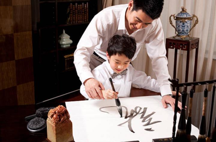 父親教導兒子習書法。(圖: Getty Images )
