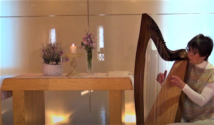 宣教士以豎琴彈奏詩歌。(圖:日本路德會神學院視頻擷圖)
