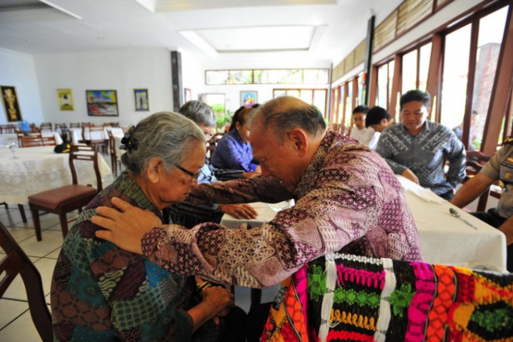唐崇榮牧師正為一婦女祈禱。(圖:印尼歸正福音教會臉書)