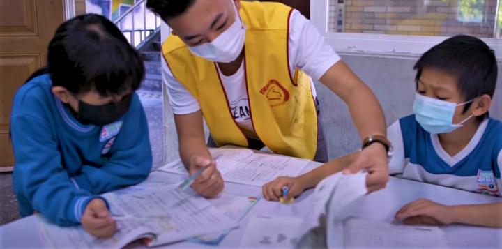 陪讀義工與學童課輔。(圖:基督教救助協會視頻擷圖)