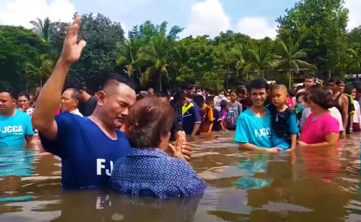 逾千在河中受浸。(圖:youtube 擷圖)