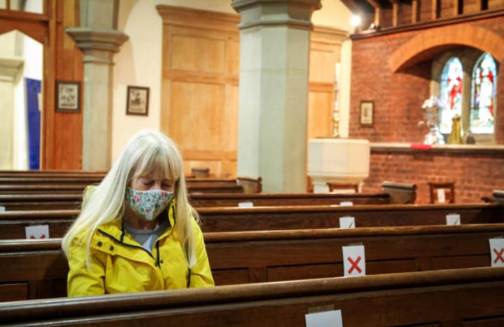 婦人戴上口罩在教堂祈禱。(圖:Getty Images)