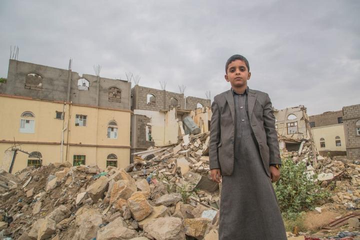 也門薩達一名兒童站在受破壞的建築物前。(圖:世界糧食計劃署)