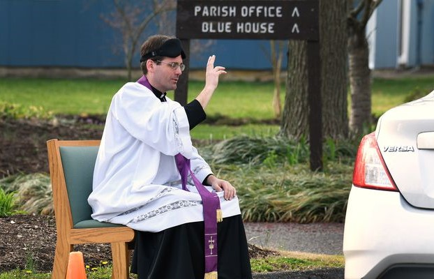 霍莫神父坐在路旁為車內教友進行快速懺悔。(圖:Capital Gazette)