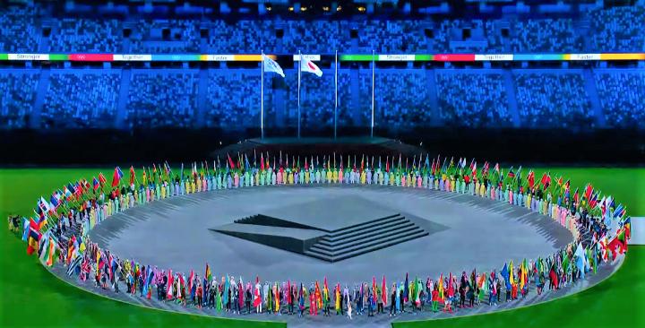 東京奧運閉幕各國選手持旗圍圈構成友愛共融的圖畫。(圖:視頻擷圖)