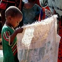一个非洲儿童手中拿着一个空的食品袋(来源:联合国世界粮食援助署) <br/>