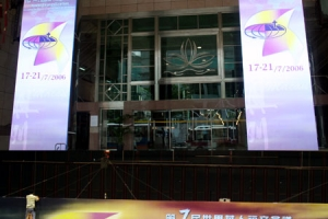 大會工作人員作最後的準備工作,在澳門綜藝館門口掛上醒目的橫額。(圖:本報記者) <br/>