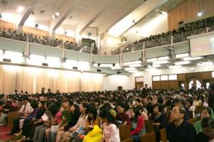 到了晚上,更多年輕的會眾下班後趕來赴會,參加唐崇明牧師主講的奮興會。(圖:本報記者) <br/>