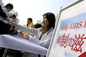 12月1日,一些醫療人員在上海街頭向行人派發愛滋病的宣傳單張及安全套。(圖:美聯社/ Eugene Hoshiko) <br/>