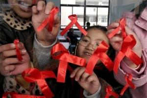 中國江蘇省南京的一所小學的學生正在把象徵關懷愛滋的紅絲帶貼上。(圖:美聯社) <br/>